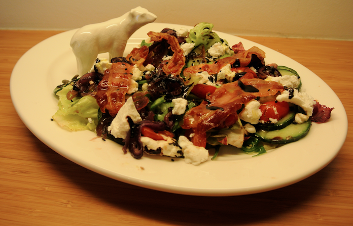 Salade geit met zwart sesam, pancetta & gekarameliseerde ui