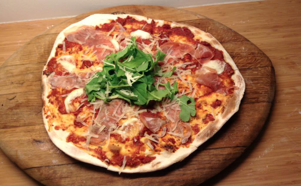 Pizza met parmaham, rucola en parmezaanse kaas