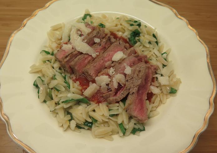 Orzo pasta met rucola en knoflooksteak